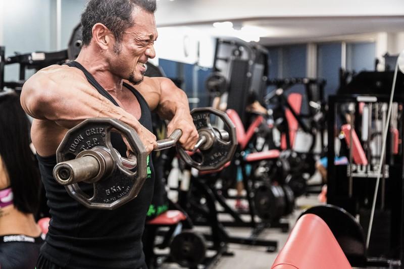 トレーニング・フィットネス・ジム・バーベルで筋肉に負荷をかけるボディビルダー